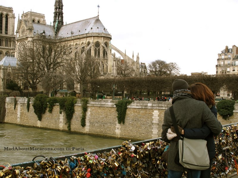 Romantic couple on the love lock bridge near Notre Dame in Paris